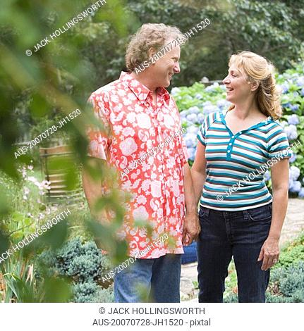 Mature couple standing in a garden and looking at each other