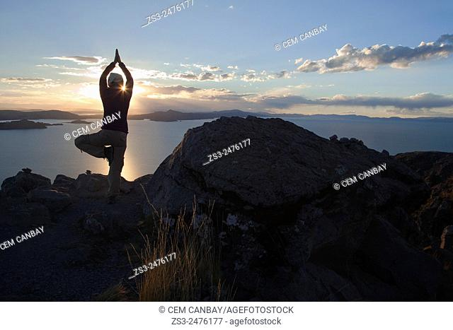 Silhouette of a tourist meditating at the top of the island of Amantani at sunset in Titicaca lake, Puno Region, Peru, South America