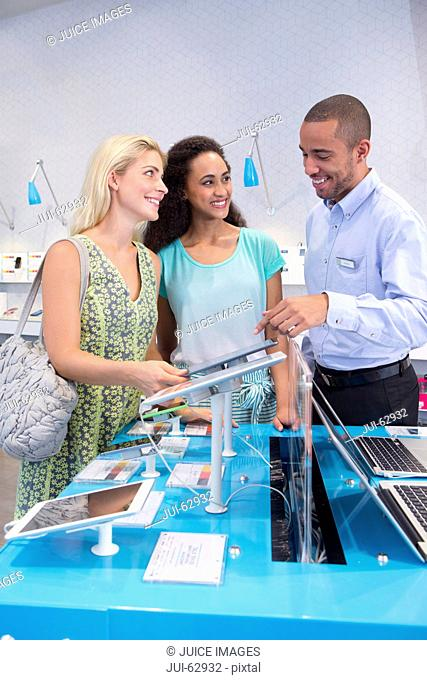 Store manager assisting two female customers in computer store