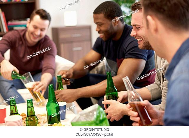 Group of men sitting in lounge holding beer bottles smiling