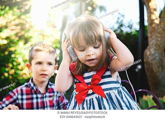 Siblings listening to music with headphones and smiling. Madrid, Spain