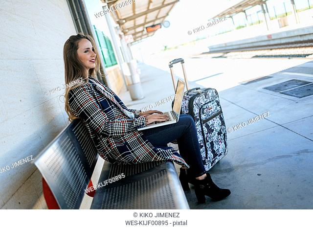 Businesswoman sitting on a bench at train station using a laptop