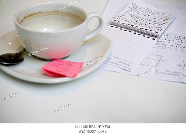 Empty cup of coffee and notepad