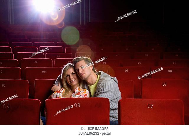 Couple cuddling in movie theater