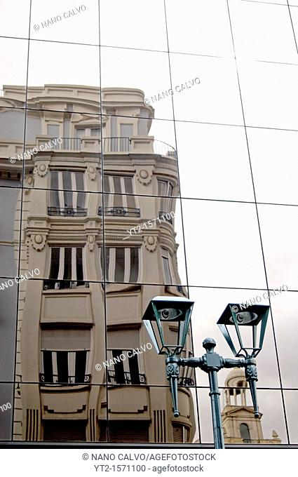 Old building reflected on the windows of another one, and street light, in Coso Area, close to Paseo Independencia, Zaragoza, Aragon, Spain