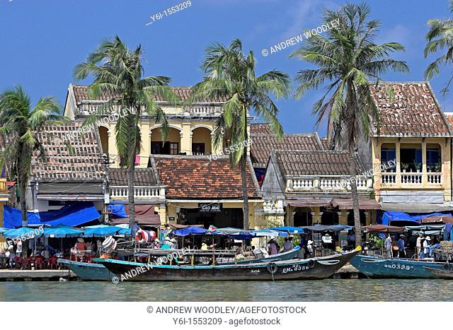 Boats palms old buildings Hoi An historic town riverfront mid Vietnam