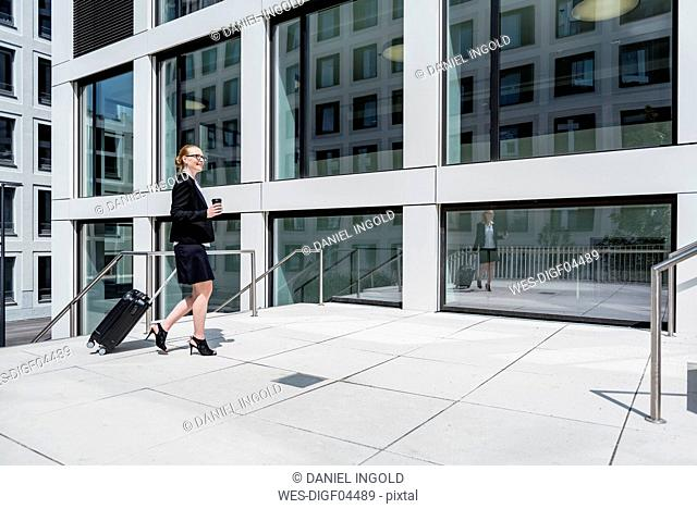 Smiling businesswoman with suitcase and coffee to go walking in front of office building