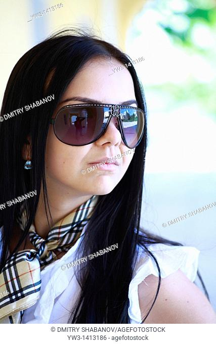 Closeup portrait of a beautiful 20-25 years happy woman in blur background outdoors with sunglasses