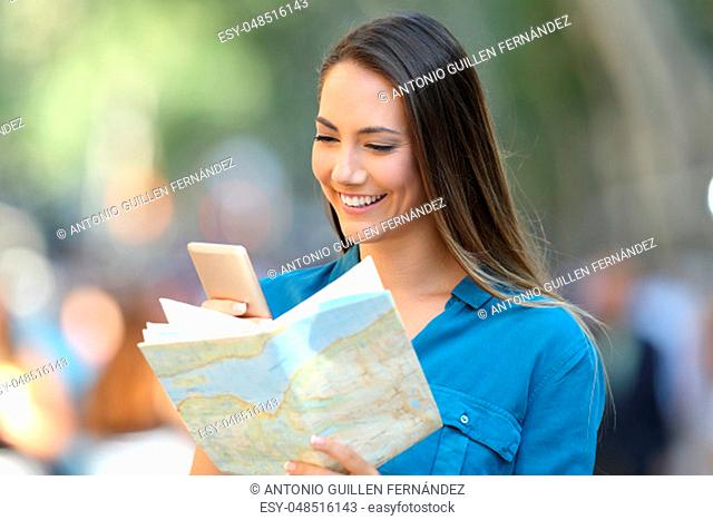 Tourist checking destination in a smart phone and a paper map in the street