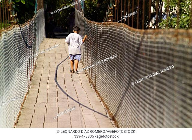 Boy crossing footbridge by Texolo waterfall, Xico. Veracruz, Mexico