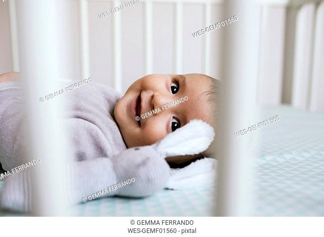 Smiling baby girl lying in crib with toy bunny