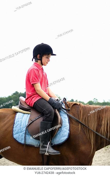 12-year-old boy riding in the fence of a riding school, Brebbia, Italy