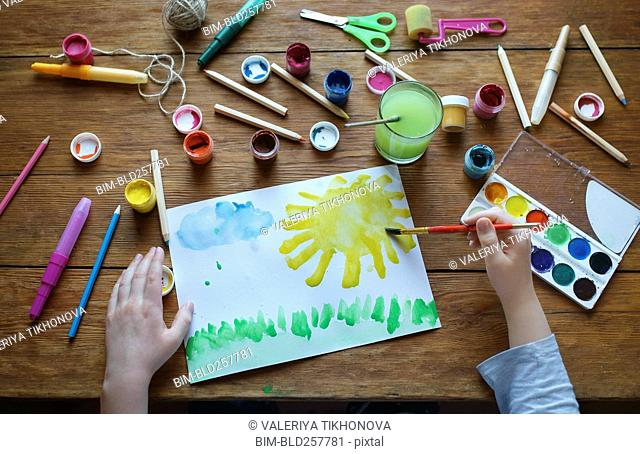 Hands of Caucasian boy painting with watercolors