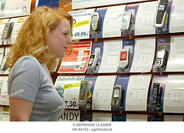 Young woman looking at mobile phones of various manufacturers in a shop. - BONN, GERMANY, 15/02/2005