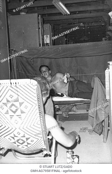 A photograph of two United States Army serviceman socializing in their barracks, one soldier is lying in bed and holding a can of Coca Cola