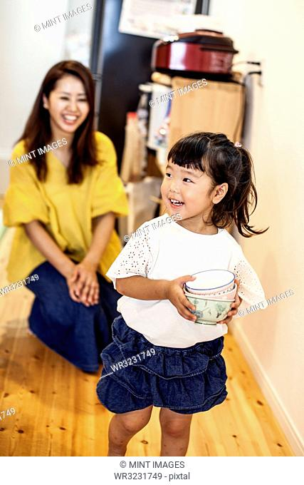 Smiling Japanese woman kneeling in a corridor behind young girl carrying stack of bowls