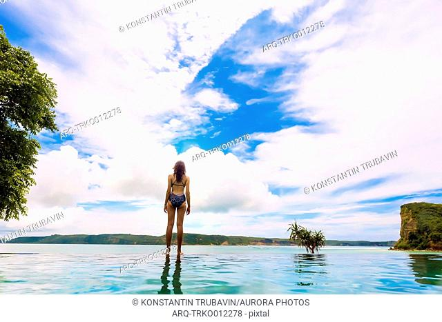 Rear view of woman in bikini standing on lakeshore against white clouds