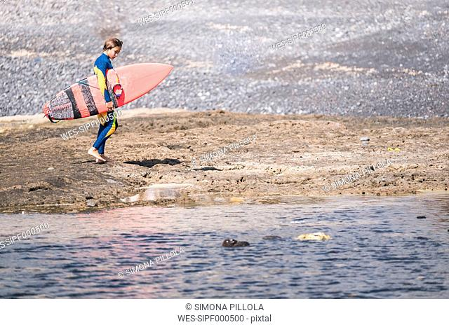Spain, Tenerife, young surfer with surfboard