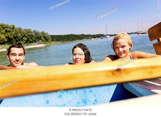 Friends with wet hair in lake holding onto boat looking at camera, Schondorf, Ammersee, Bavaria, Germany