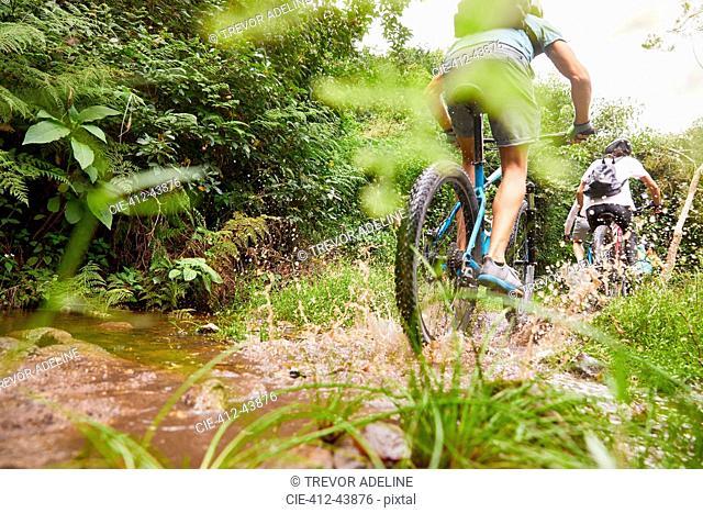 Man mountain biking, splashing on muddy trail