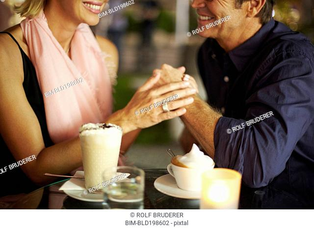 Couple holding hands over coffee in restaurant