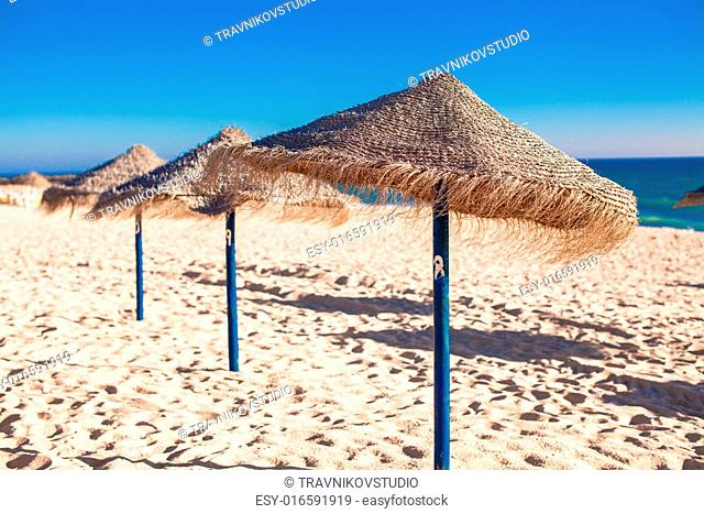 Straw umbrellas on empty tropical beach on the Atlantic coast