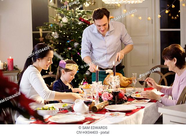 Multi-generation family carving Christmas turkey at candlelight dinner table