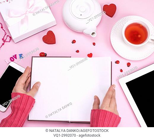 Open book with blank white sheets in female hands, top view