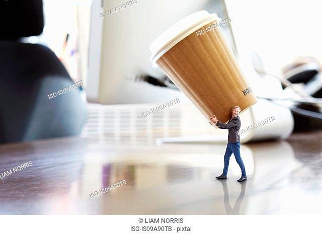 Mature businessman carrying large disposable cup on oversized desk