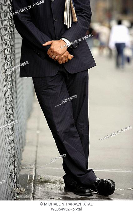 Business man with paper under arm leaning on fence neck down