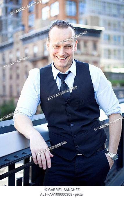 Businessman standing on balcony, smiling, portrait