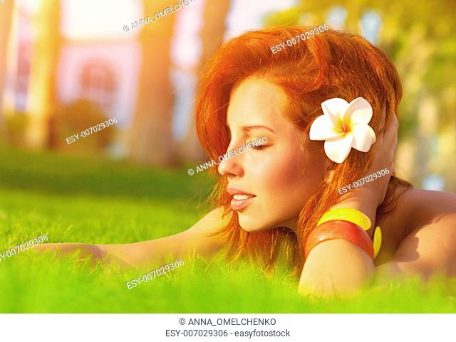 Profile of attractive woman with closed eyes dreaming outdoors, lying down on fresh green grass glade, frangipani flower in red hair, enjoying day spa