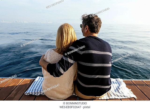 Mature couple sitting on jetty, relaxing at the sea