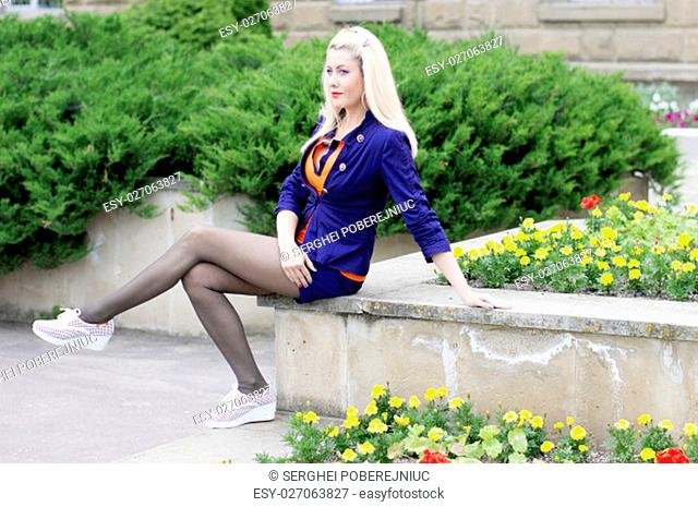 the beautiful woman sits at a flower lawn, a subject beautiful women in the summer