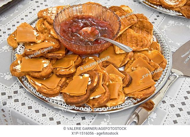 This traditional Norwegian food, is a silver platter of heart shaped waffles with slices of brown goat cheese on top  In the center of the platter is a crystal...
