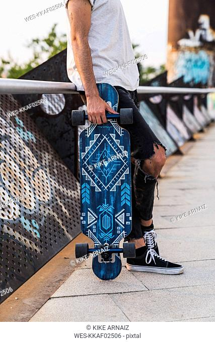 Close-up of man with skateboard outdoors