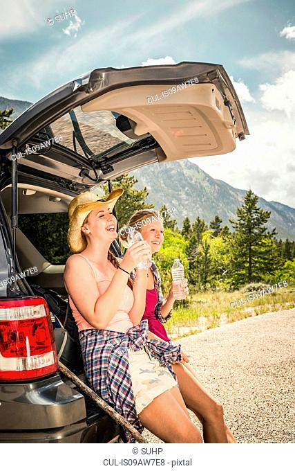 Young woman and teenage girl hiker drinking water on car boot, Red Lodge, Montana, USA