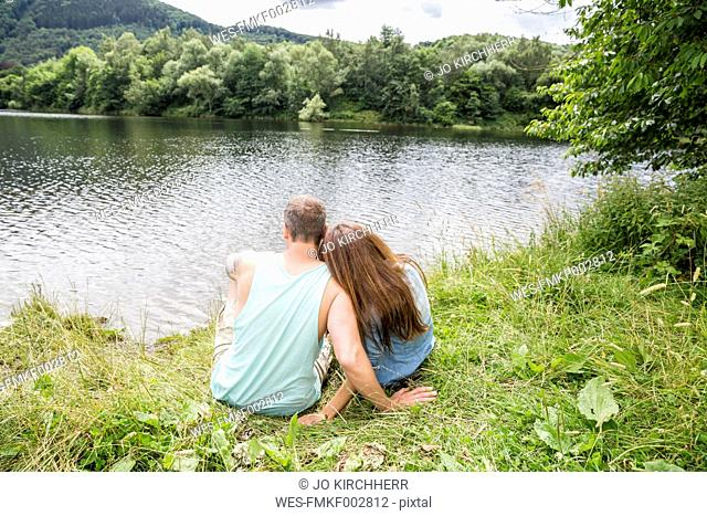 Couple sitting at lakeside