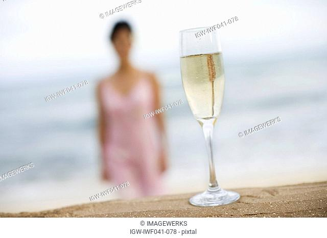 Close-up of a wineglass on sand