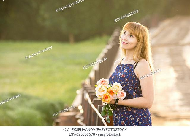 Young girl with a bouquet of roses standing on the bridge in the background blurred foliage