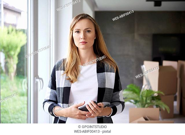 Portrait of serious woman moving into new flat