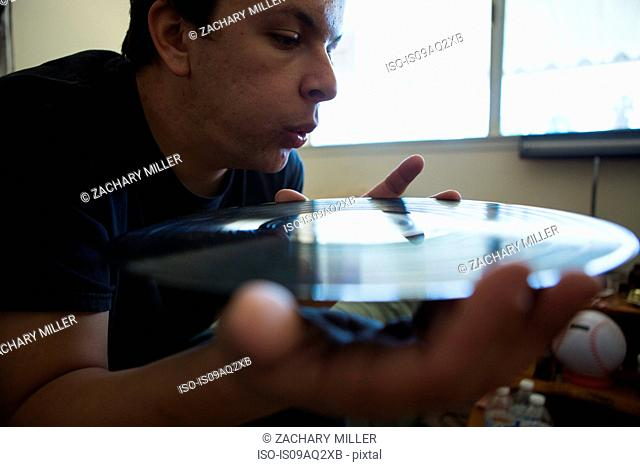 Close up of young man blowing surface of vinyl record