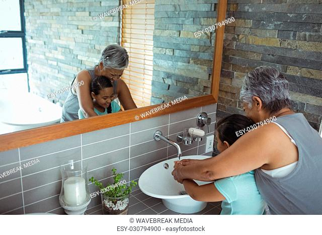 Grandmother and granddaughter washing hands in bathroom sink