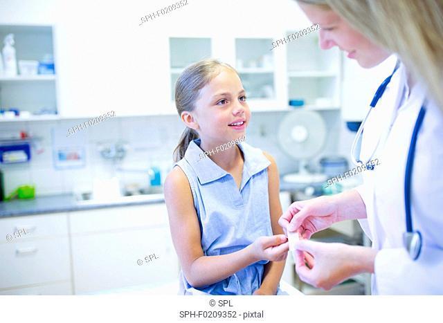 Doctor applying plaster to girl's finger