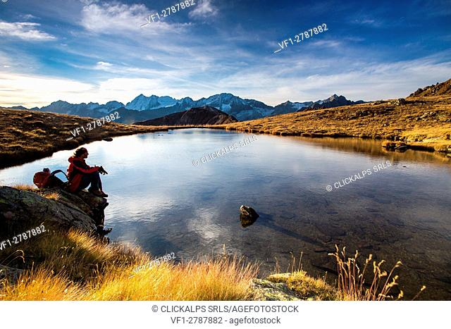 A hiker enjoying the first daylights in front of the landscape of Adamello-Presanella - Tonale mount, Lombardy, Italy. Europe