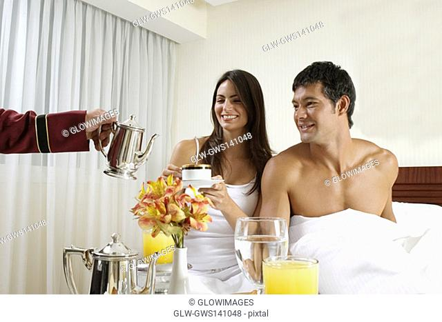 Person's hand serving tea to a young woman and a mid adult man on the bed