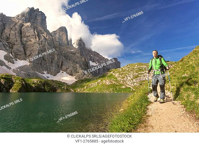 Europe, Italy, Veneto, Belluno. Hiker passes near Lake Coldai along the CAI 560, which at this point coincides with the Alta Via n. 1 of the Dolomites