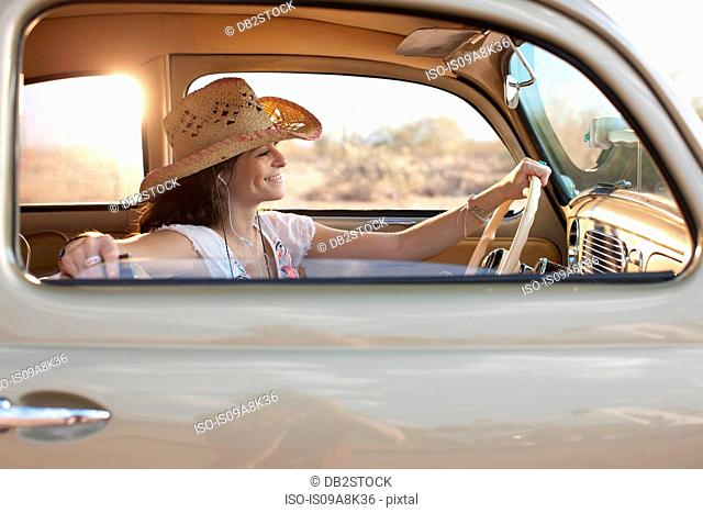 Young woman sitting in car on road trip, smiling