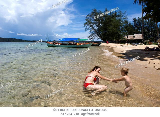 Beach on the island of Koh Russei. Cambodia. Travel with children's. Mother playing with her daughter. Koh Russei, also named Koh Russey or Bamboo Island is a...