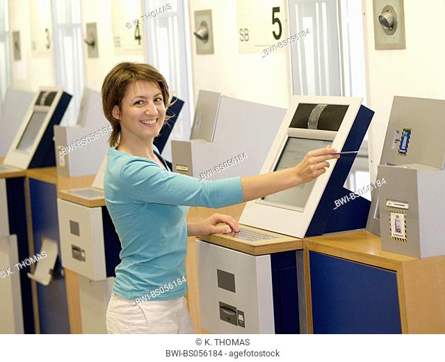 young woman standing at the terminal in front of a computer, inserting a card into the machine